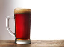 Frosty mug of dark beer. On wooden table Stock Images
