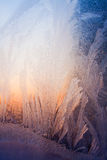 Frosty natural pattern and sunlight. Frosty natural pattern at a winter window glass, sunset Stock Photography