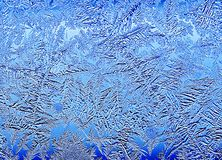 Frosty natural pattern on winter window.Frost patterns on glass.Blue toned ice patterns. Winter ice embroidered lace on the window Stock Photography