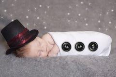 Frosty the newborn snowman. A beautiful sleeping newborn wearing a Frosty the snowman costume stock image