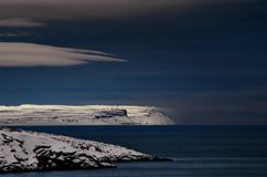 Frosty night landscape the Arctic Ocean. Northern severe cold nature cliffs. Dark deep blue water and sky, white clouds. Black rocky shore. The Barents Sea stock photos