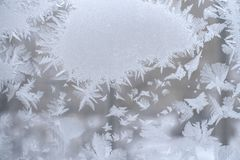Frosty pattern in form of spot and beautiful pointed snowflakes around it on winter window pane. Royalty Free Stock Photos