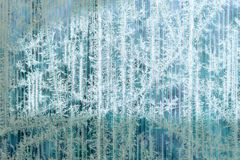 Frosty pattern of hoarfrost and snowflakes on striped glass, winter or Christmas background, texture royalty free stock photo