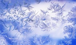 Frosty pattern with various ornate patterns on the transparent glass on the winter window in delicate lilac and blue. Beautiful frosty pattern with various stock photos