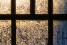 Frosty pattern on the window. Glass lit by sunlight royalty free stock photos