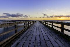 Frosty Pier. Early morning light on a frosty ocean pier and an orange glow in the sky.Victoria Canada royalty free stock image