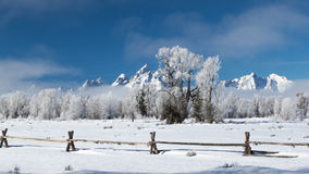 Frosty ranch wooden fence jagged mountains Stock Images