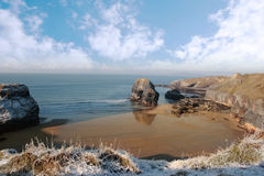 Frosty snowcovered coast beach and virgin rock Stock Images