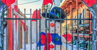 Frosty the Snowman Behind Bars. Blow up Frosty the Snowman doll behind a gate waving during the holidays stock photo
