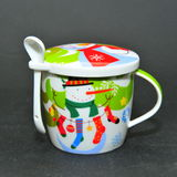 Frosty the snowman ceramic cup with cover and spoon. Christmas tea cup isolated on black background stock photo