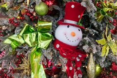 Frosty the Snowman ornament on a Christmas tree. Frosty the Snowman ornament and a shiny green ribbon on a Christmas tree stock photo