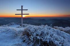A frosty sunset in mountains with cross Royalty Free Stock Photography