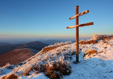 A frosty sunset in mountains with cross Royalty Free Stock Images