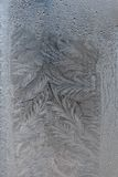 Frosty texture on glass. Frost on the glass, frozen water on glass, frost paints on glass Royalty Free Stock Photos