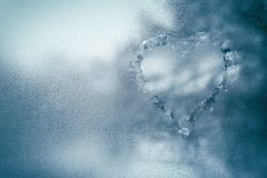 Misted window, raindrops on the window close up, Ice blue background. Frosty window with a heart icon in winter. Heart sign on a misted window. Abstract stock photography