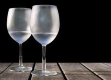 Frosty wine glasses. On outdoor table - black background Stock Photo