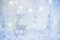 Frosty winter wonderland with toy deer, snowfall and magic lights. stock images