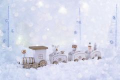 Frosty winter wonderland with toy train, snowfall and magic lights. Christmas greetings concept stock images