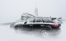 Black family car on a snowy mountain peak. Frosty wintry scene with the sport utility vehicle standing inside cloud at the top of the hill in mountains Stock Images
