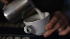 Frothed mjölkar hälls in i en kopp kaffe Cappuccinoförberedelse lager videofilmer