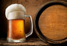 Frothy beer and barrel. Frothy beer and wooden barrel in clay cellar Stock Images