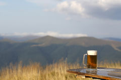 Frothy beer. One glass mug with lager or porter tasty frothy beer on wooden table top sunny day outdoor on natural with mountain hills and yellow dry grass and Stock Image