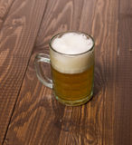 Frothy beer on table Stock Image