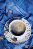 Frothy black coffee on a vintage lacy saucer. Fine white porcelain cup of frothy black coffee on a vintage lacy saucer with a silver teaspoon, on blue velvet Royalty Free Stock Images