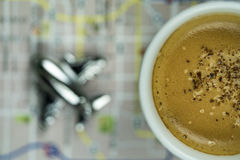 Frothy Cappuccino on Map with Silver Airplane royalty free stock photo