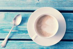 Frothy coffee - cappuccino in a white mug on a blue wooden backg Stock Images
