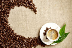 Frothy coffee cup, beans,leaf twisted in swirl on flax Stock Images