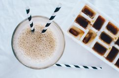 Frothy ice coffee in glass with drinking straw Stock Photos