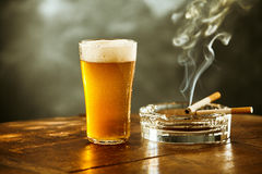 Frothy ice cold beer and cigarette in a pub. Frothy ice cold beer in a tall glass and two burning cigarettes resting on an ashtray in a pub with wafting tendrils Stock Photos