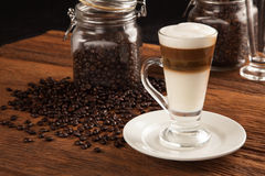 Frothy, layered cappuccino in a clear glass mug Stock Image