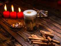 Frothy, layered cappuccino in a clear glass mug. Three red candles, cinnamon sticks and sweets. Romantic concept Stock Photo