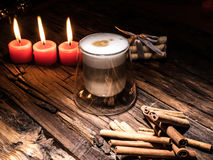 Frothy, layered cappuccino in a clear glass mug. Three red candles, cinnamon sticks and sweets. Romantic concept Stock Photos