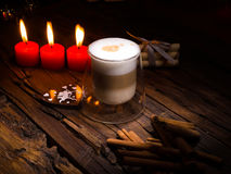 Frothy, layered cappuccino in a clear glass mug. Three red candles, cinnamon sticks and sweets. Romantic concept Stock Photography