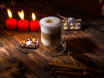 Frothy, layered cappuccino in a clear glass mug. Three red candles, cinnamon sticks and sweets. Romantic concept Royalty Free Stock Photo