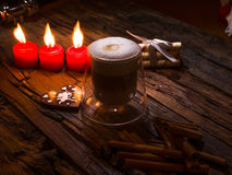 Frothy, layered cappuccino in a clear glass mug. Three red candles, cinnamon sticks and sweets. Romantic concept Stock Image