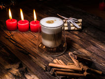 Frothy, layered cappuccino in a clear glass mug. Three red candles, cinnamon sticks and sweets. Romantic concept Royalty Free Stock Photography