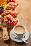 Frothy milky coffee with tostada snacks. Frothy milky cappuccino coffee with tostada snacks topped with salsa, ham and tuna served on a rustic wooden chopping Stock Photo