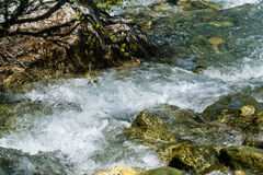 Frothy mountain stream stones wrapped. Foamy, turbulent mountain stream passes through rocks with rock pattern Stock Photo