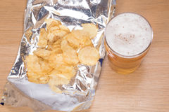 Frothy pint of lager and open bag of potato chips. A high angle view of a freshly poured, frothy pint of lager beer beside an open foil packet of potato chips on Stock Images