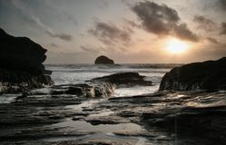 Frothy sunset. Taken at trebarwith strand cornwall, the frothy nature of the sea that evening combined with the rocks leads you into the picture, with the sunset Royalty Free Stock Photo