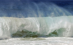 Frothy wave crashes on shore at Aliso Beach in Laguna Beach, California. Stock Photography