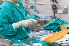 Frottez l'infirmière préparant des outils pour la chirurgie cardiaque ouverte images libres de droits