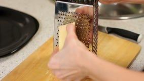 Frottez le fromage sur une râpe sur la table de cuisine écrasement du fromage Fromage discordant de femme Préparation de pizza banque de vidéos