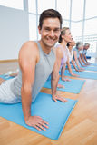 Froup doing cobra pose in row at yoga class Stock Images