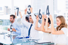 Froup of panel judges holding score signs Stock Image