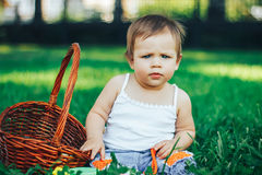 Frown baby girl looking at the camera. Baby is seriously looking into the camera. She frowns. Sitting on grass. outdoor Stock Image